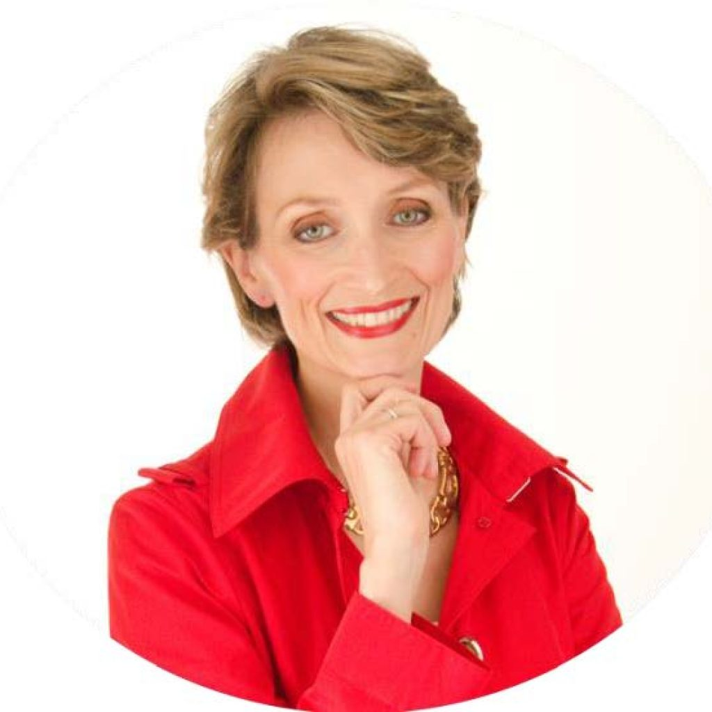 Psychologist Clare Mann in a red shirt with red lipstick and gold jewellery. She has short blond hair and hazel eyes.